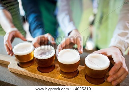 Midsection of friends reaching towards beer sampler at bar counter