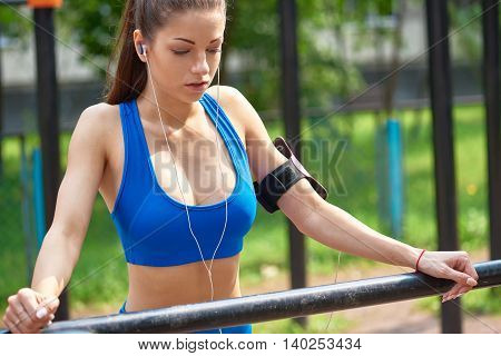 Sporty young woman concentrating before outdoor exercise.