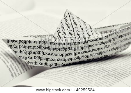 closeup of a paper boat, made with a printed paper with non-sense words, on an open book