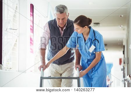 Nurse helping senior man with walking aid in a retirement home