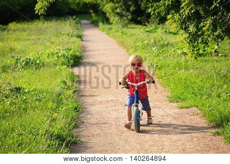 cute little girl riding runbike in summer, kids sport