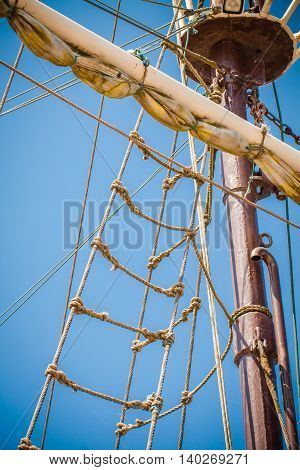 The mast of old ship with sail and ladder made of rope.
