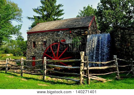 Sudbury Massachusetts - July 12 2013: The Old Stone Grist Mill with water wheel and cascade still grinds flour for nearby Longfellow's Wayside Inn