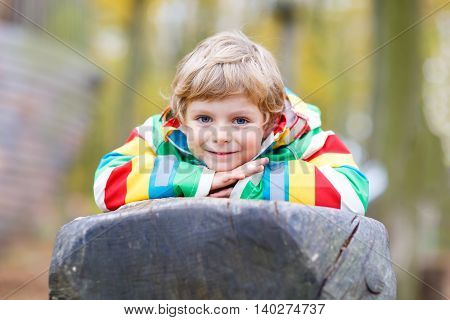 Little kid boy in colorful rain jacket with stripes and gumboots having fun with playing on playground on warm, autumn day, outdoors