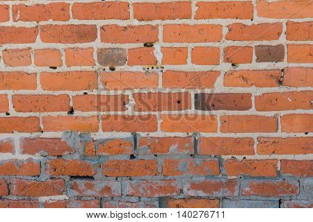 A closeup of a red, weathered brick wall.