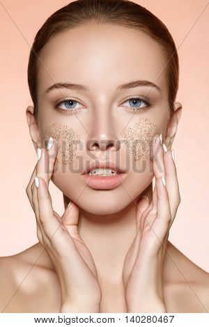 Attractive young girl rubs a skin scrub on the cheeks. Close-up portrait on a beige background.