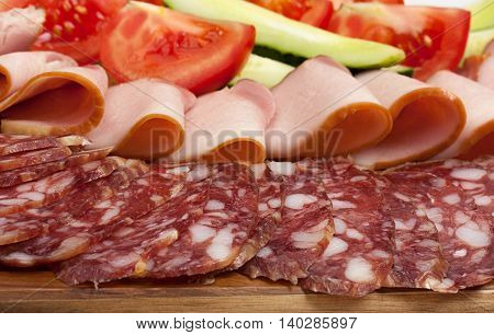Sliced dry sausages and meat products cured meat bacon with fresh cucumber tomatoes slices on a wood board.