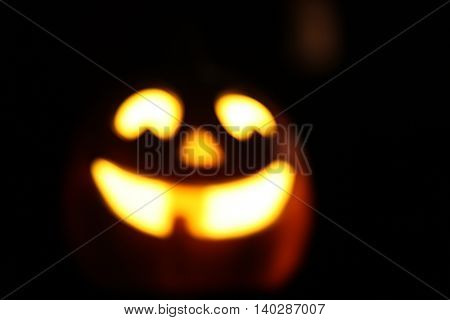 blurred image of a smiling Halloween jackolantern decoration glowing in the evening toned with a retro vintage instagram filter app or action