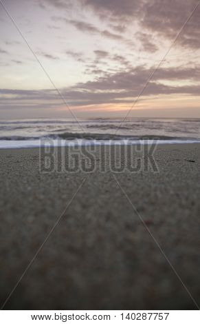 Sunrise on an empty beach with clouds, waves and sand, Outer Banks North Carolina