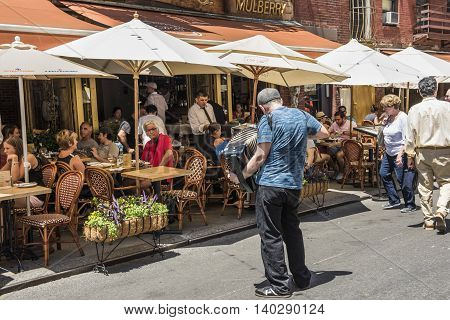 New York City, USA - June 18, 2016: Man plays accordian by restaurant in Little Italy