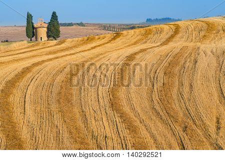 VITALETA, ITALY - JULY 7:  The wheat fields and the Capella di Vitaleta or Vitaleta Chapel near the village of vitaleta in Tuscany Italy on July 7, 2016.