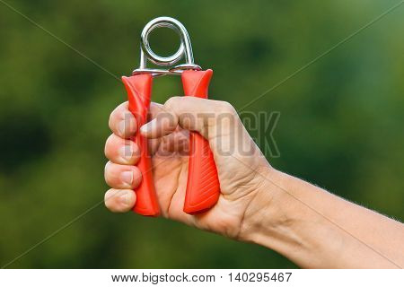 hand doing exercises with hand grip on green blurred background