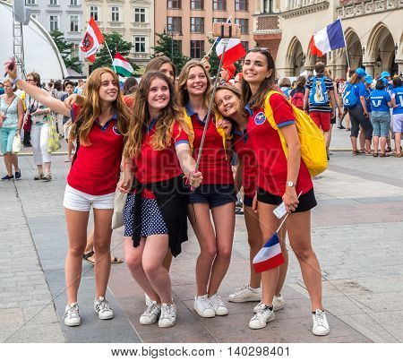 KRAKOW POLAND - JULY 27 2016: A group of French girls in red female pilgrims taking selfies on the Market Square in Cracow during the World Youth Day 2016