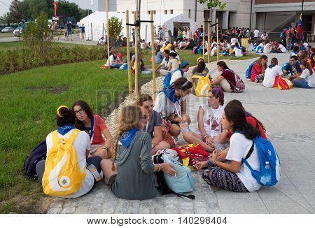 KRAKOW POLAND - JULY 26 2016:. World Youth Day 2016. Young people from various countries sitting on the ground and talking in small groups around the Sanctuary of Pope John Paul II.