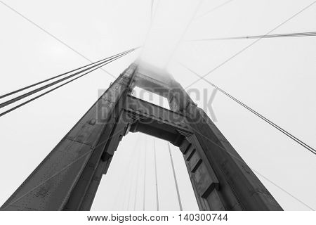 Golden Gate bridge tower emerging from iconic San Francisco bay fog bank in black and white.