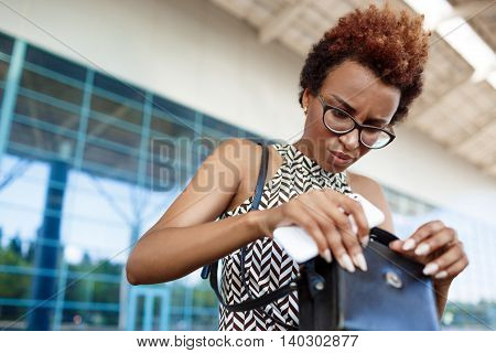 Young successful african businesswoman in glasses rummaging in bag, holding phone, standing  over business centre.