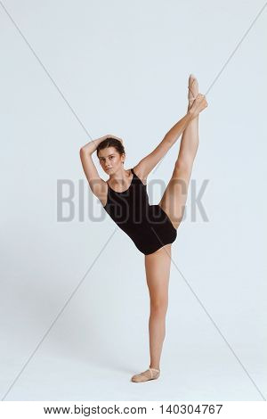 Young beautiful contemporary brunette dancer looing at camera, posing over white background. Copy space.