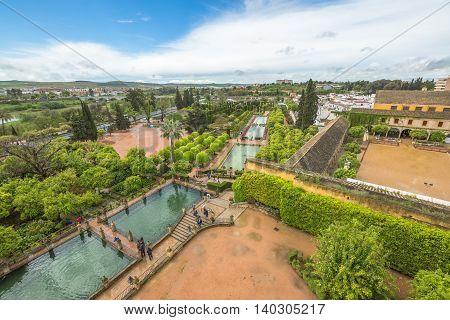 Cordoba, Andalusia, Spain - April 20, 2016: tourists walking along the popular gardens of Alcazar de los Reyes Cristianos. Aerial view and skyline of Cordoba city.