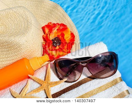 Beach hat sunglasses bath towel sun spray starfish near the swimming pool