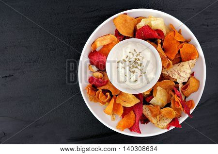 Plate Of Colorful Organic Vegetable Chips With Dip Overhead View On A Slate Background