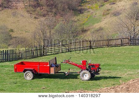 Red behind tractor stands in the farmyard. Agriculture