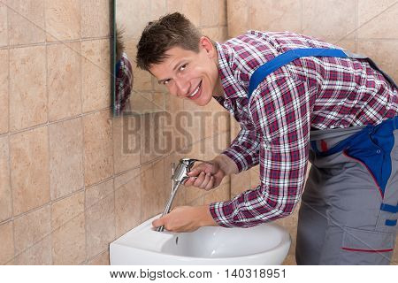 Young Male Plumber Hand Fixing Tap Of Sink In Bathroom