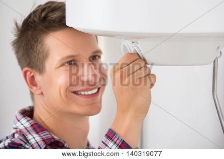 Smiling Young Male Plumber Adjusting Temperature Of Electric Boiler