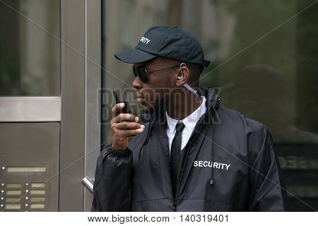 Portrait Of Young African Male Security Guard Talking On Walkie-Talkie