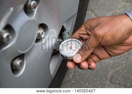 Close-up Of Person Hand Holding Pressure Gauge For Measuring Car Tyre Pressure
