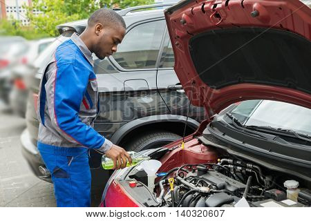 Young African Mechanic Pouring Oil Lubricant Into The Car Engine