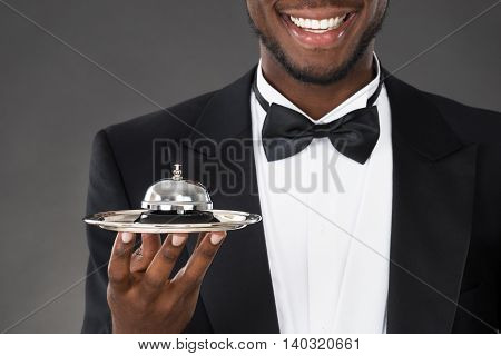 Portrait Of Happy African Waiter Holding Service Bell