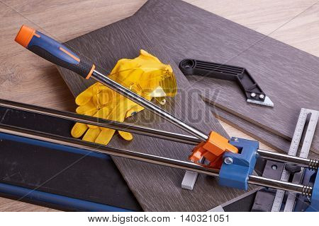 Manual cutter  and ceramic tiles for floor. Home repair.