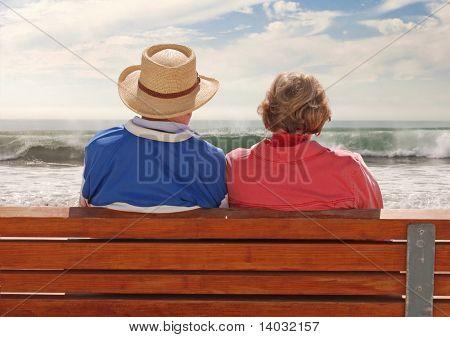 A senior adult Couple sitzen an einem Benchand, genießen ihre Zeit am Strand.