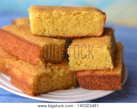 Cornbread Slices Stacked on a White Plate set against a Blue Background