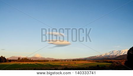 Tongariro volcano and unusual (UFO looking) cloud in dusk time, New Zealand