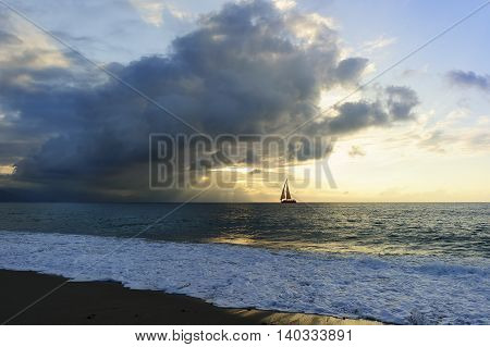 Sailboat silhouette is a burst sun beams shooting out through the clouds as a sailboat moves along the water towards the light.