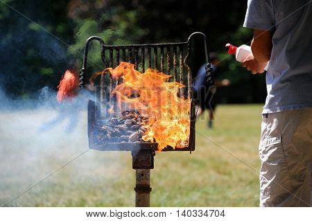 man start barbecue and igniting the coal by fire starter