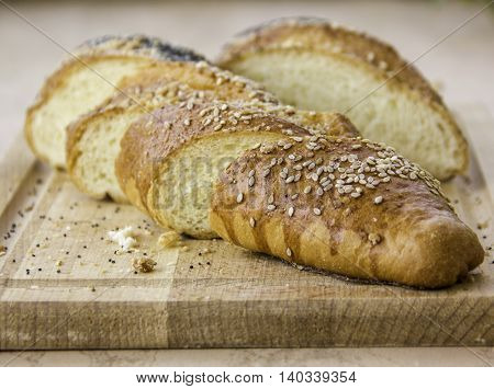 fresh baked long loaf with sesame and poppy seeds on wooden table