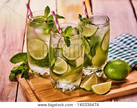 Alcohol drink. On wooden boards three glasses with alcohol drink and ice cubes. Drink two hundred eighty six cocktail mohito with straw and lime and mint leaf. Country life. Boards light background.