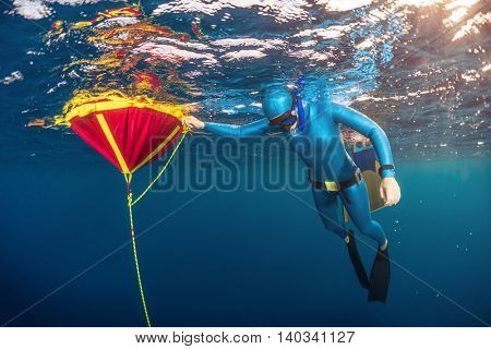 Underwater shot of lady freediver training in sea with buoy