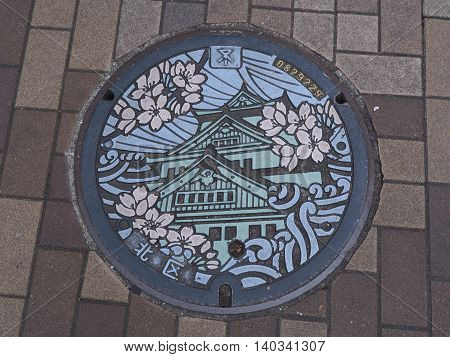 OSAKA, JAPAN - JUNE 09, 2016: A manhole cover in Osaka, Japan. The Osaka castle and sakura engraved on to a manhole cover as a symbol of an important city's landmark.