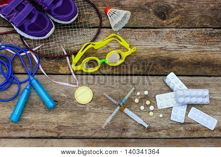 Sports equipment: racket, skipping rope, swimming goggles, sneakers, sports medal and medicines on wooden background. Toned image