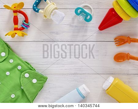 Babies goods: cloth diaper, baby powder, nibbler, cream, teether, soother, baby spoon and fork, pyramid toy on white wooden background with copy space. Top view or flat lay