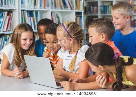 School kids using laptop in library at school