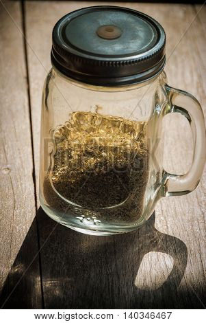 Minced Origano spice herb in glass container with shade