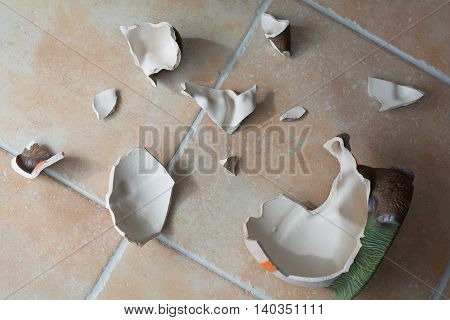 decorative ceramics figure is broken on tile floor
