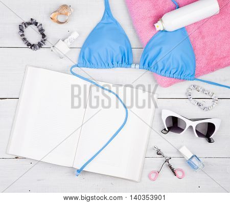 Blue Swimsuit, Book, Pink Towel, Cosmetics Makeup, Bijou And Essentials On White Wooden Desk