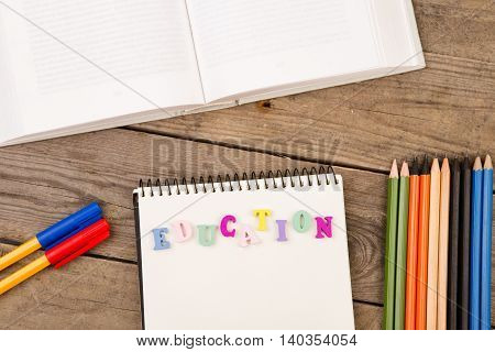 "School Set With Inscription Of ""education"", Book, Notepad, Pencils And Pens On Brown Wooden Table"