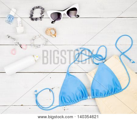 Blue Swimsuit, Yellow Shorts, Cosmetics Makeup, Bijou And Essentials On White Wooden Desk
