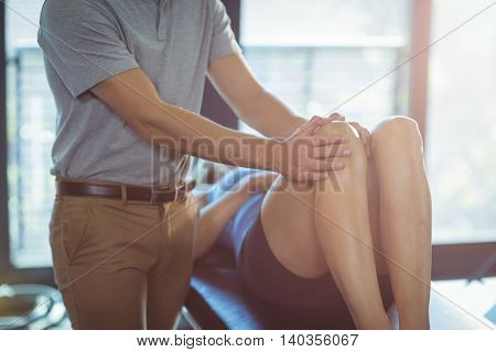 Physiotherapist giving knee massage to a woman in clinic